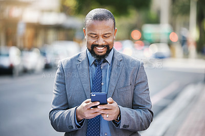 Buy stock photo Shot of a businessman using his cellphone while out in the city