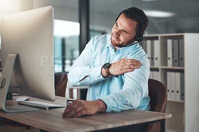 Buy stock photo Shot of a young call centre agent sitting alone in his office and suffering from a sore shoulder