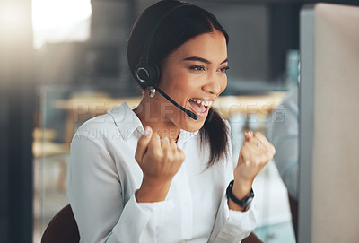 Buy stock photo Shot of a young call centre agent sitting alone in her office and celebrating a success