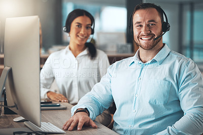 Buy stock photo Shot of two young call centre agents sitting together in the office and using a computer