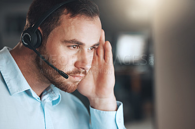 Buy stock photo Shot of a young call centre agent sitting alone in his office and looking contemplative while using his computer