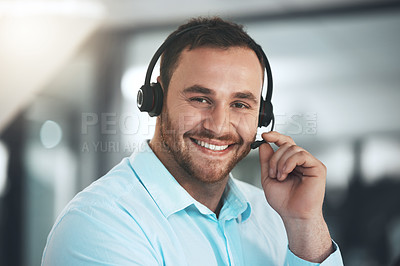 Buy stock photo Shot of a young call centre agent sitting alone in his office