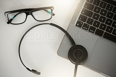 Buy stock photo Aerial shot of a laptop and headset on a table in an office at work