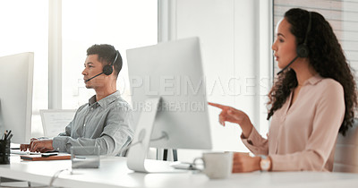 Buy stock photo Shot of two young call center agents working in an office