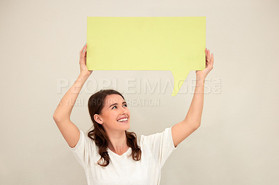 Buy stock photo Shot of a young woman holding up a sign against a white background