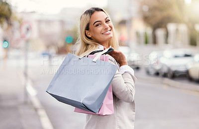 Buy stock photo Rearview portrait of an attractive young woman walking with her bags over her shoulder while out shopping in the city