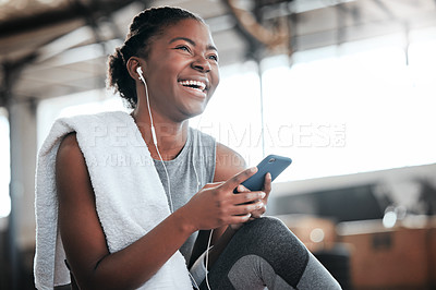 Buy stock photo Shot of a young beautiful woman using her cellphone and earphones at the gym