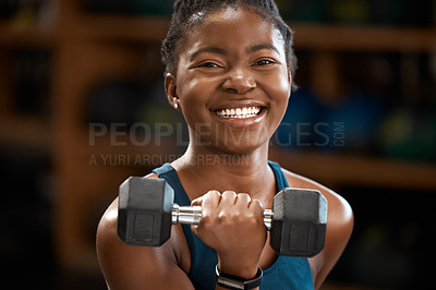 Buy stock photo Cropped portrait of an attractive and athletic young woman working out with a dumbbell in the gym
