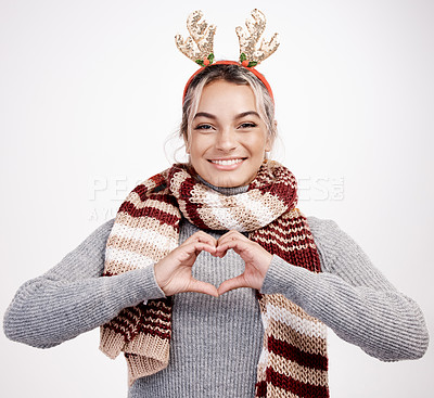 Buy stock photo Studio portrait of an attractive young woman making a heart shape with her hands while dressed in Christmas-themed attire
