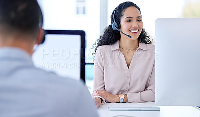 Buy stock photo Shot of a young call centre agent sitting with her colleague and using her computer