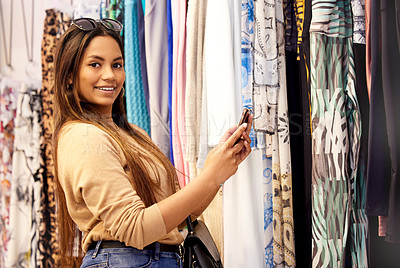 Buy stock photo Shot of a beautiful young woman using her cellphone while out shopping