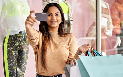 Buy stock photo Cropped portrait of an attractive young woman holding up a credit card while shopping in the city