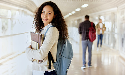 Buy stock photo Cropped portrait of an attractive young female college student standing with her textbooks in a campus hallway