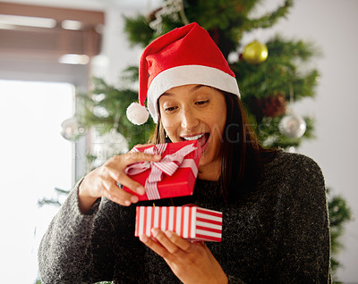 Buy stock photo Shot of a young woman opening presents during Christmas at home