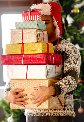 Buy stock photo Shot of a young man carrying a stack on gifts at home