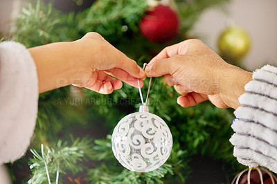 Buy stock photo Shot of an unrecognizable woman decorating a Christmas tree at home