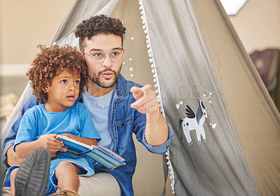 Buy stock photo Shot of a father reading to his son