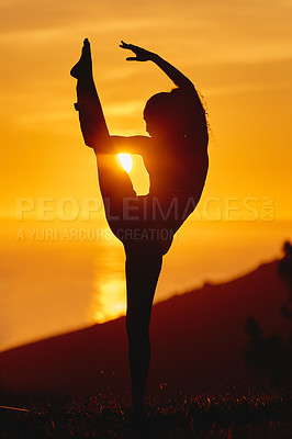 Buy stock photo Full length shot of an unrecognizable and athletic young woman practicing yoga outside at sunset