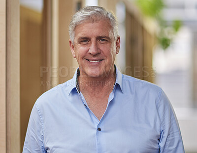 Buy stock photo Cropped portrait of a handsome mature businessman standing in a hallway in his office