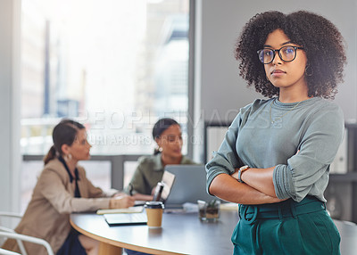 Buy stock photo Portrait of a young businesswoman folding her arms while her colleagues have a meeting in the background