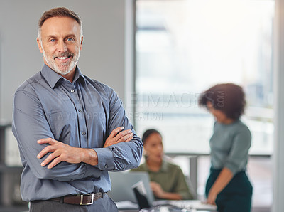 Buy stock photo Portrait of a mature businessman at the office standing in front of his colleagues having a meeting in the background