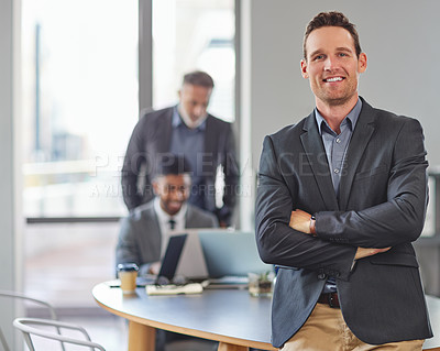 Buy stock photo Portrait of a young businessman at the office standing in front of his colleagues having a meeting in the background