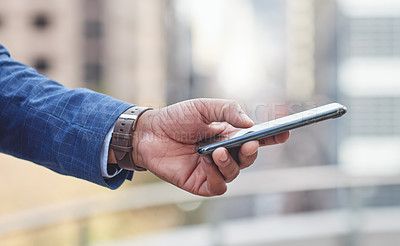 Buy stock photo Cropped shot an unrecognizable businessman using his cellphone outside
