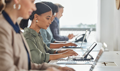 Buy stock photo Shot of a young businesswoman working on a digital tablet alongside her colleagues in a call centre