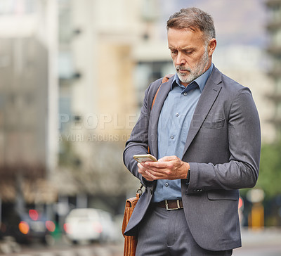 Buy stock photo Shot of a mature businessman using his smartphone to send a text message
