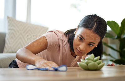 Buy stock photo Shot of a young woman cleaning a table at home
