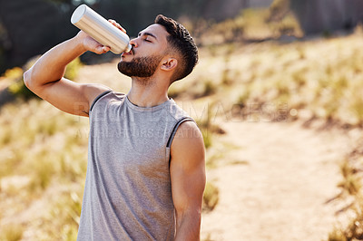 Buy stock photo Shot of a handsome young man standing alone outside and drinking water during his run