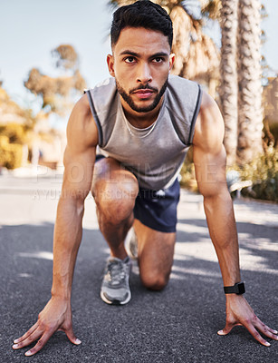 Buy stock photo Full length shot of a handsome young man crouched in a start position before running outside