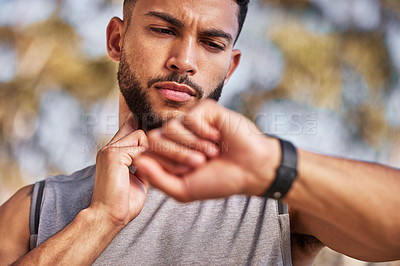 Buy stock photo Shot of a handsome young man standing alone outside and using his watch to time his pulse after a run