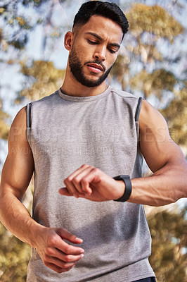 Buy stock photo Shot of a handsome young man looking at his watch during his outdoor run