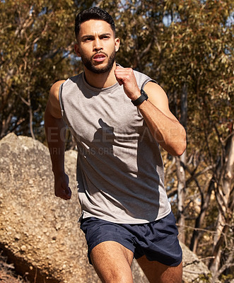 Buy stock photo Shot of a handsome young man running alone outdoors