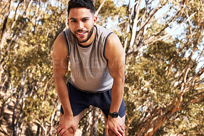 Buy stock photo Shot of a handsome young man taking a moment to catch his breath during his outdoor run