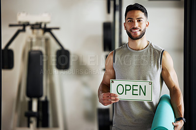 Buy stock photo Portrait of a young man holding up an open sign in his gym