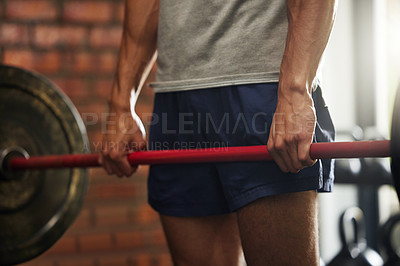 Buy stock photo Shot of an unrecognisable man working out with a barbell in a gym