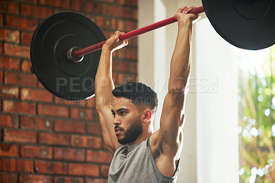 Buy stock photo Shot of a young man working out with a barbell in a gym