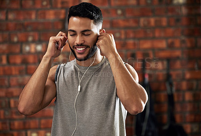 Buy stock photo Shot of a young man stretching using earphones during his workout in the gym