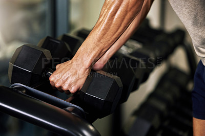 Buy stock photo Shot of an unrecognisable man working out with dumbbells in a gym