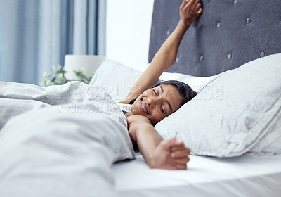 Buy stock photo Shot of a young woman stretching while lying in her bed