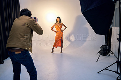 Buy stock photo Shot of a photographer taking photos of a model in a studio
