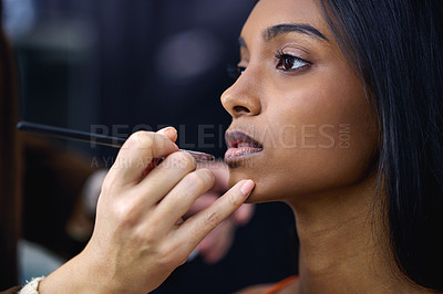 Buy stock photo Shot of a young woman having her lipstick touched up during a photoshoot