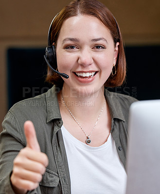 Buy stock photo Shot of a young call centre agent sitting alone in the office and making a thumbs up gesture
