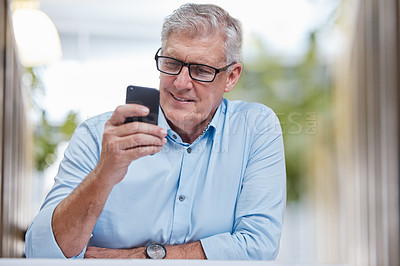 Buy stock photo Shot of a mature businessman sitting alone in the office and using his cellphone