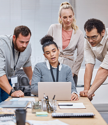 Buy stock photo Shot of a diverse group of businesspeople having a meeting in the office and using a laptop