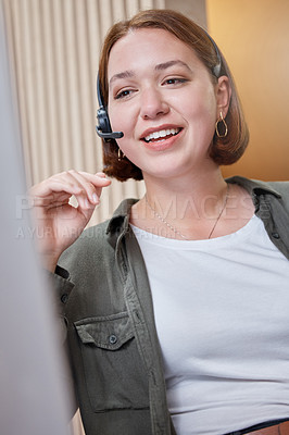 Buy stock photo Shot of a young call centre agent sitting alone in the office and using her computer