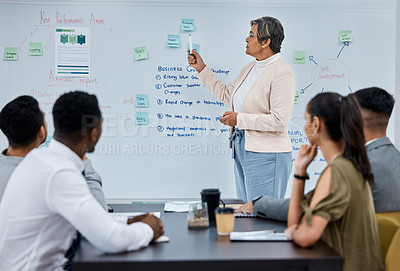 Buy stock photo Shot of a mature businesswoman using a whiteboard during a presentation to her colleagues in an office