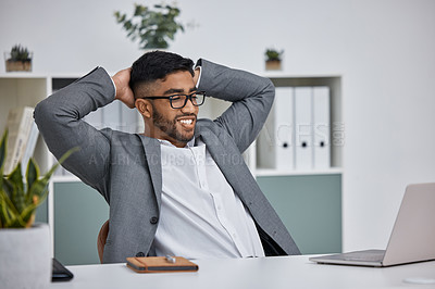 Buy stock photo Shot of a young businessman sitting with his hands behind his head in an office